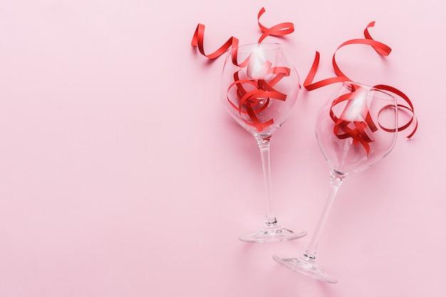 Deux verres à vin avec des rubans rouges sur fond rose avec espace de copie