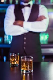 Deux verres de whisky sur le comptoir et le barman