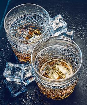 Deux verres de whisky coûteux avec de la glace sur un plateau en pierre noire
