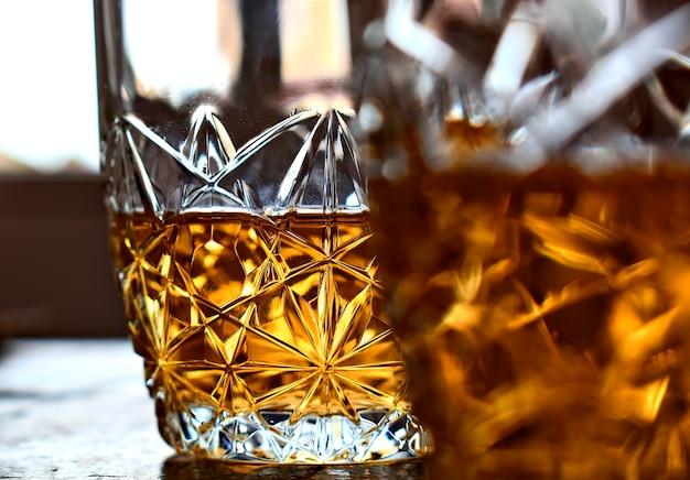 Deux verres de whisky sur une vieille table en pierre et fond d'une fenêtre lumineuse.