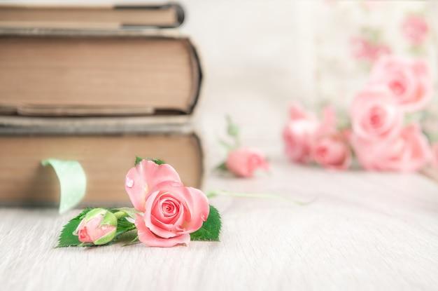 Deux vieux livres sur table en bois parmi de jolies petites roses roses, fond de texte