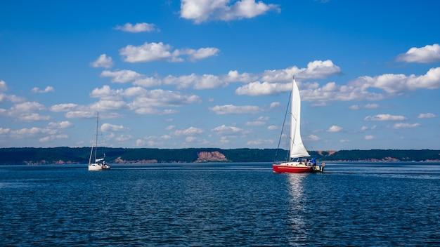 Deux voiliers, blanc et rouge, sur la rivière.