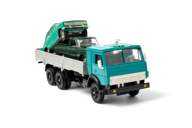 Deux voitures chargées dans la carrosserie d'un camion à plateau sur fond blanc