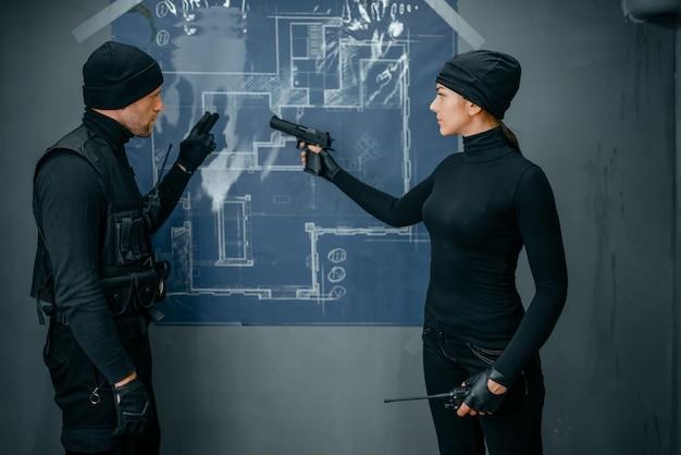 Deux voleurs travaillant sur un plan pour voler le coffre-fort