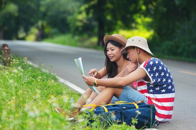 Deux voyageurs assis sur une rue de campagne