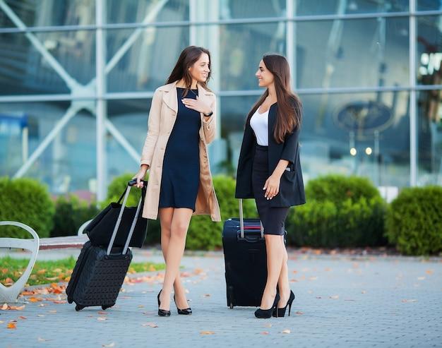 Deux voyageurs élégantes marchant avec leurs bagages à l'aéroport
