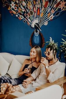 Deux voyageurs féminins et masculins s'amusent à boire un café ensemble dans une luxueuse chambre d'hôtel. vacances en thaïlande.