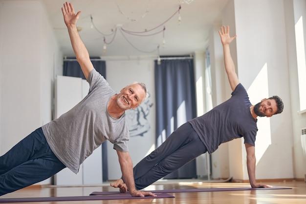 Deux yogis souriants supportent le poids de leur corps sur une main et un pied
