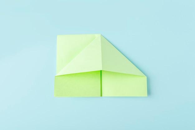 Deuxième étape de la fabrication d'un papillon en papier origami avec du papier vert, des ciseaux sur fond bleu