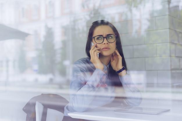 Devant la fenêtre, une femme est assise à une table et parle au téléphone