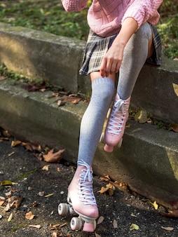 Devant, vue, femme, poser, escalier, à, chaussettes, et, patins a roulettes