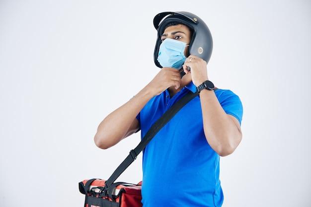 Develiry homme en masque médical avec sac isotherme sur son épaule mettant un casque
