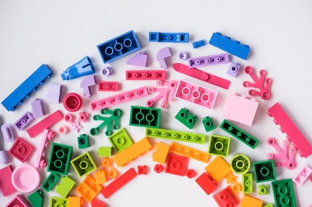 Développement du cadre de jeux pour enfants. briques et blocs en plastique colorés sur fond blanc, vue du dessus, espace pour le texte. jouet éducatif pour les enfants.