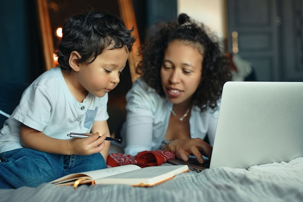 Développement précoce, éducation, enfance et gadgets électroniques modernes. portrait de jeune femme latine attentionnée sur le lit à l'aide d'un ordinateur portable