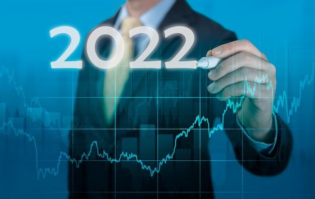 Développements de succès de croissance dans le concept 2022. homme d'affaires en costume d'analyse de prévision graphique des bénéfices avec stylo et augmentation des indicateurs positifs. graphique de l'année du plan financier de l'entreprise.
