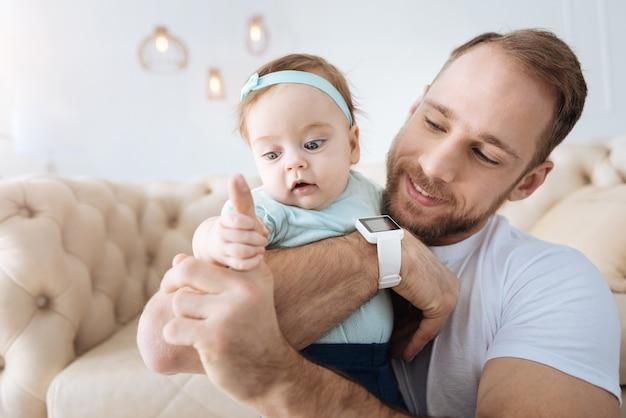 Développer notre réflexe. joyeux père barbu heureux assis à la maison et tenant la petite fille dans ses bras tout en exprimant ses soins et en jouant avec son enfant