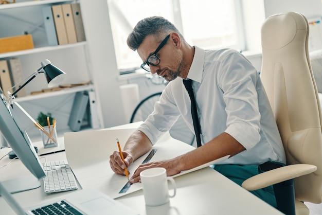 Développer un nouveau projet. vue de dessus du beau jeune homme dessinant quelque chose alors qu'il était assis au bureau