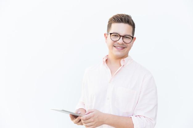 Développeur d'applications convivial positif posant avec tablette