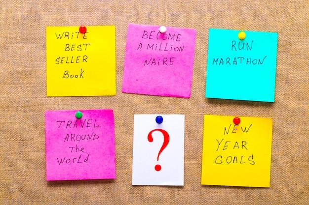 Devenez millionnaire et d'autres objectifs ou résolutions irréalistes du nouvel an - notes autocollantes colorées sur toile