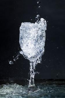 Déversement de verre d'eau sur fond sombre