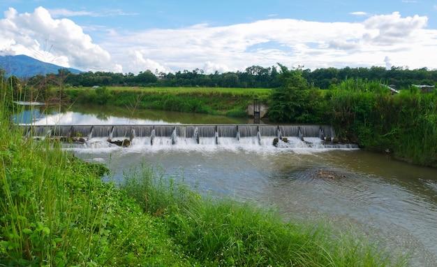 Déversoir du niveau supérieur jusqu'au niveau inférieur. stockage d'eau à usage agricole avec forêt en arrière-plan