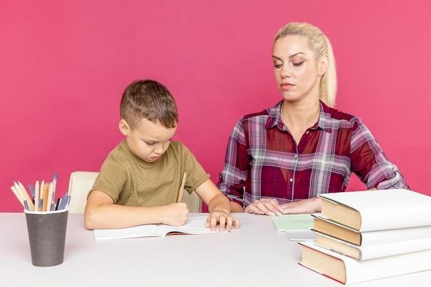 Devoirs à distance avec la mère à la maison au moment de la quarantaine. garçon avec maman assise au bureau et étudie.
