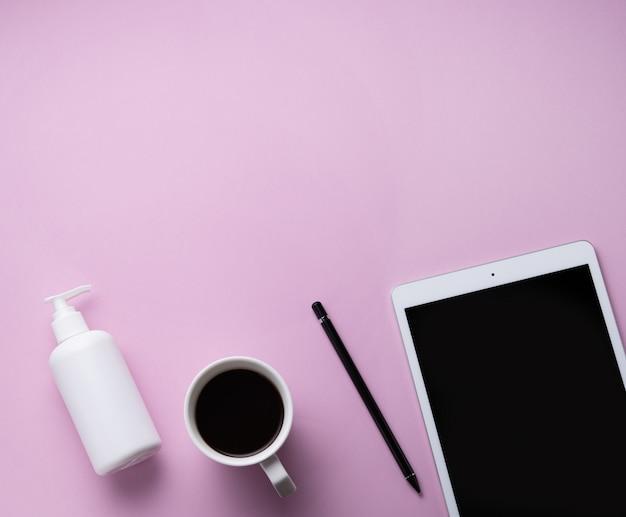 Devoirs. mise à plat d'affaires avec une tasse de café, un désinfectant et une tablette sur fond rose