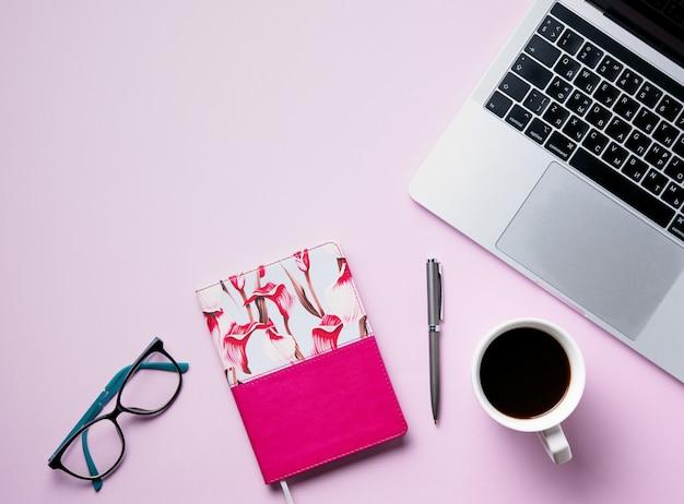 Devoirs. mise à plat d'affaires avec une tasse de café, note, crayon, lunettes, cahier sur fond rose