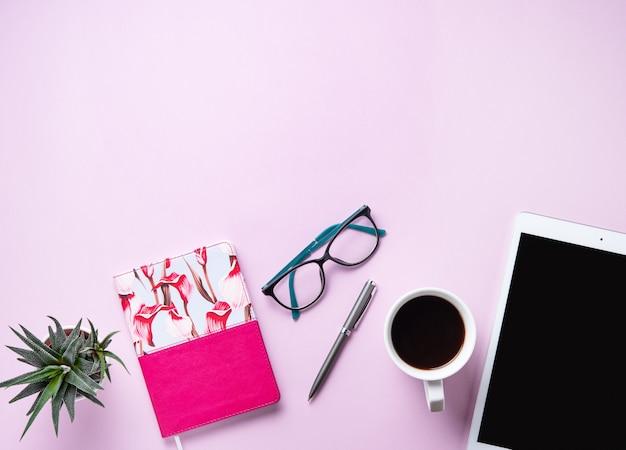 Devoirs. mise à plat d'affaires avec tasse de café, note, crayon, lunettes, tablette et sicculent sur fond rose