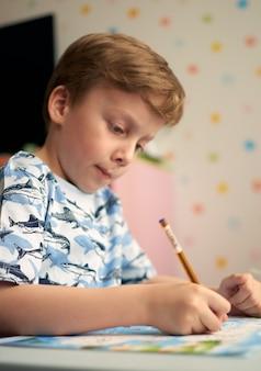 Devoirs pendant la leçon en ligne à la maison, quarantaine sociale à distance covid-19, auto-isolement, concept d'éducation en ligne, enseignement à domicile. enfant à la maison, jardin d'enfants fermé, homelerning. garçon de 6 ans.