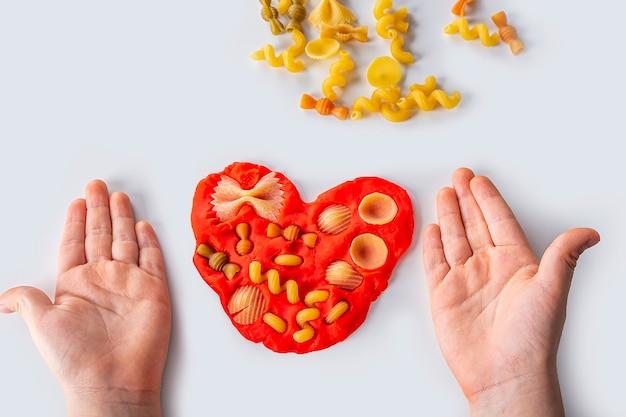 Dextérité. créativité des enfants. modélisation de la pâte à modeler pour le développement de l'enfant à la maison. childs mains créant le cœur de la pâte pour la modélisation. jeu anti-stress avec des pâtes.