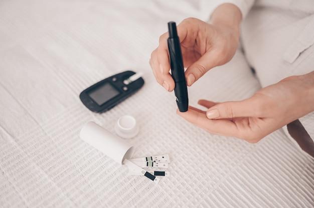 Diabète vérifiant la glycémie. femme à l'aide de lancette et glucomètre numérique à la maison. médecine, diabète de régime, concept de soins de santé - mains féminines avec glucomètre vérifiant le niveau de glucose corporel
