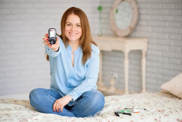 Diabète vérifiant le taux de sucre dans le sang. femme à l'aide de lancelet et glucomètre à la maison.