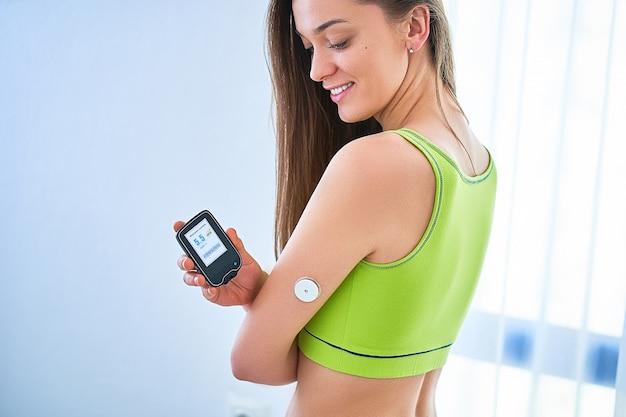 Diabétiques femme vérifiant le niveau de glucose avec un capteur à distance. surveillance continue et contrôle des niveaux de glucose sans sang. technologie dans le traitement du diabète et les soins de santé
