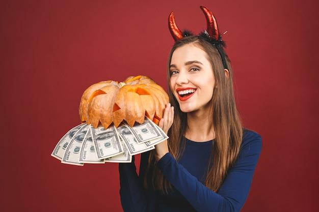 Diable d'halloween avec une citrouille sculptée et de l'argent - isolé sur fond rouge. émotionnelle jeune femme en costume d'halloween.
