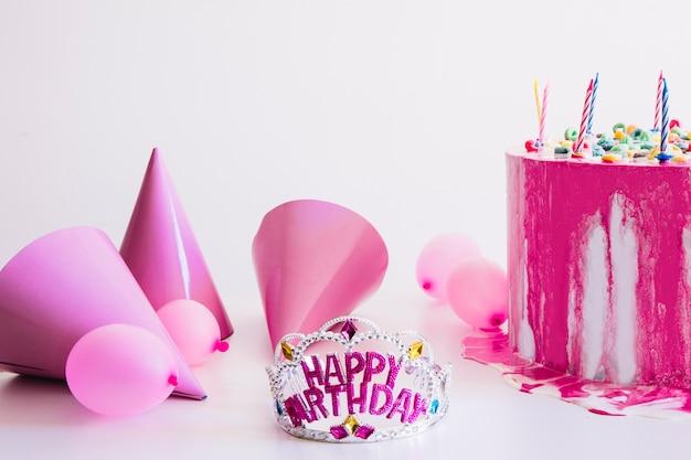 Diadème d'anniversaire près de fournitures de fête et gâteau
