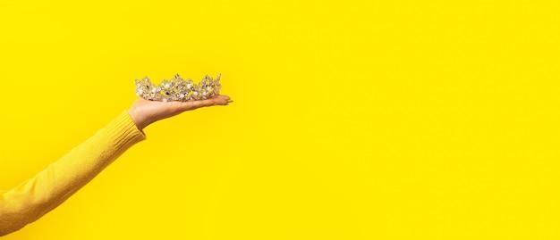 Diadème brillant sur main féminine sur jaune