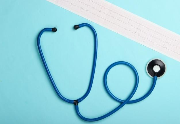 Diagnostic et prévention (traitement) des maladies cardiovasculaires. cardiogramme cardiaque, stéthoscope sur fond bleu. coeur en bonne santé. vue de dessus