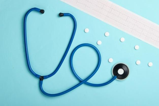 Diagnostic et prévention (traitement) des maladies cardiovasculaires. cardiogramme cardiaque, stéthoscope, pilules sur fond bleu. coeur en bonne santé. vue de dessus
