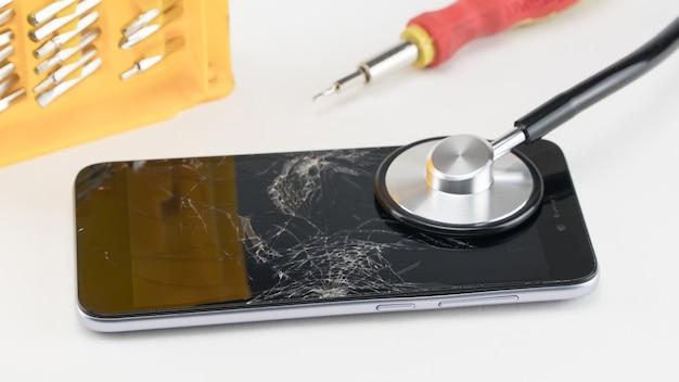 Diagnostiquer le téléphone avec un stéthoscope, près d'un tournevis. concept de réparation de téléphone