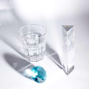 Diamant bleu; long cristal et verre d'eau avec une ombre sur fond blanc