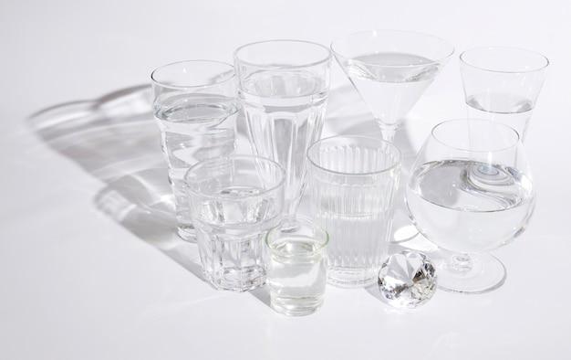 Diamant brillant avec des verres d'eau sur fond blanc