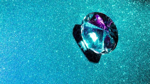 Diamant en cristal sur fond de paillettes turquoises brillantes