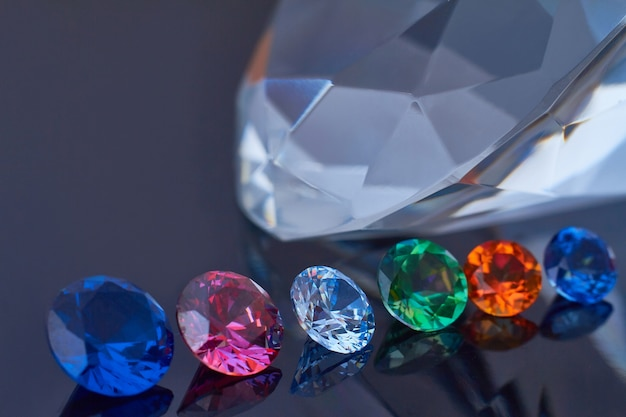 Diamant énorme et plusieurs cristaux chics sur une surface de miroir noire, scintillant et brillant