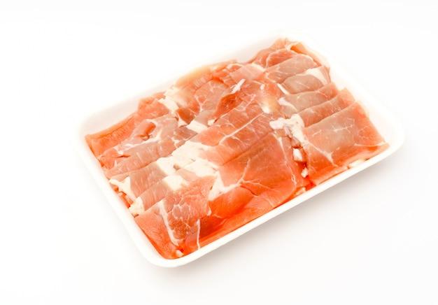 Diapositive de porc cru sur fond blanc.