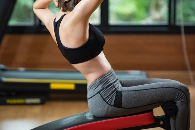 Diapositive vue de femme de remise en forme avec course sur la machine de tapis roulant dans la salle de gym.