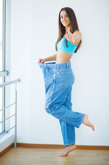 Diète. belle femme sportive montrant combien de poids elle a perdu.