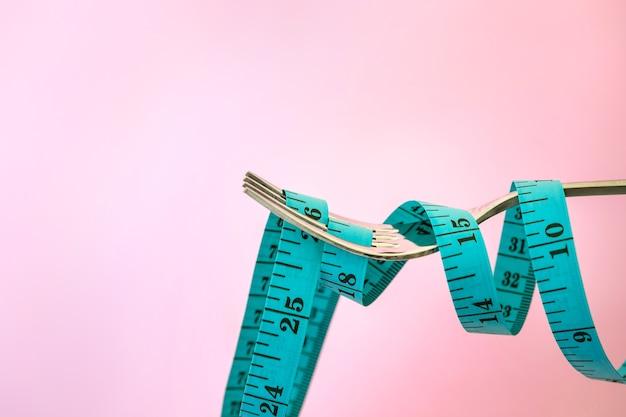 Diète pour la perte de poids, ruban à mesurer avec une fourchette sur un fond rose clair