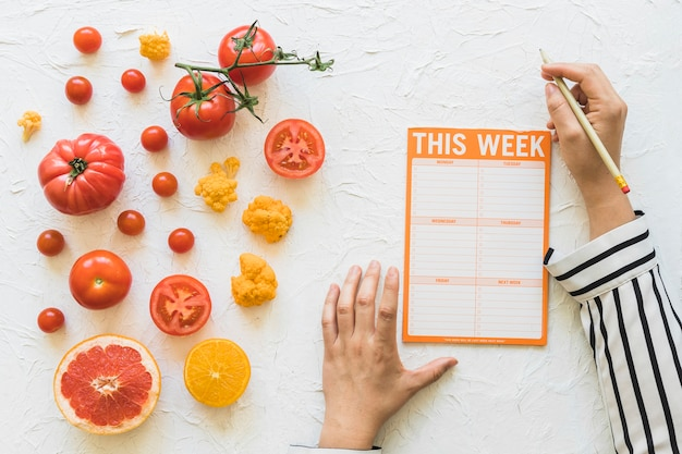 Diététicien planification semaine de régime avec des légumes et des fruits sur fond blanc
