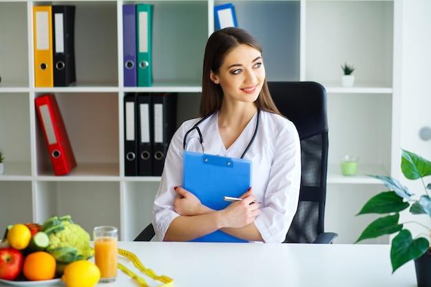 Diététiste de jeune femme assise à une table avec des fruits et des légumes frais.